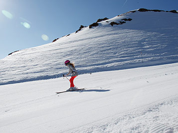 Enfant qui ski sur une pistes pendant ses vacances au ski